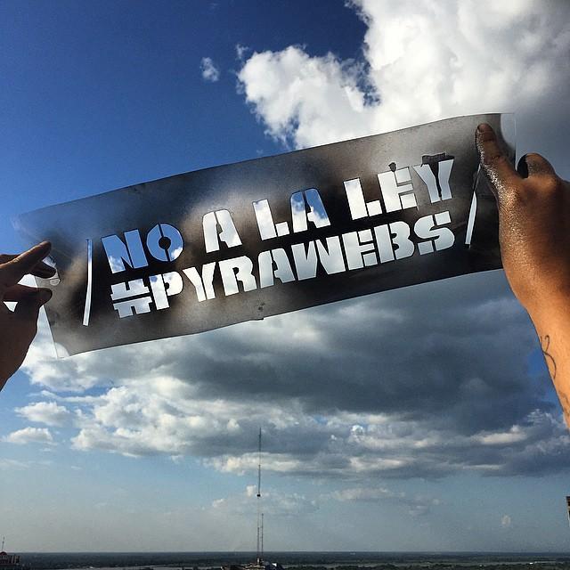 """Se observan dos manos sosteniendo un cartel """"No a la ley #Pyrawebs"""" y de fondo el cielo"""