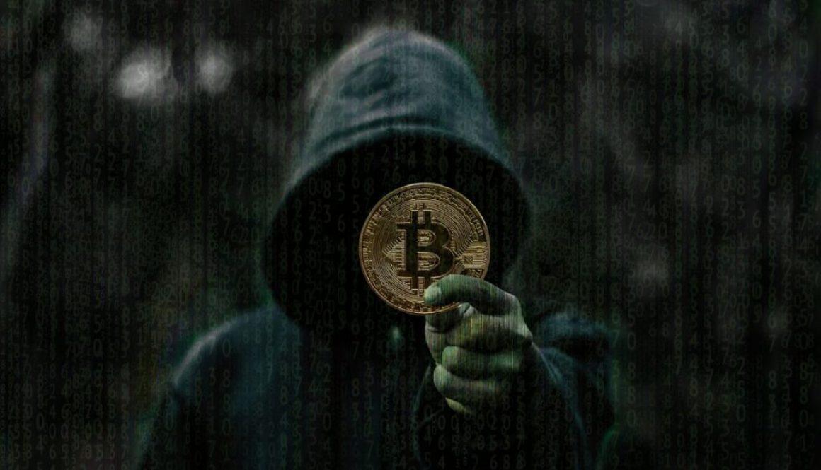 Persona encapuchada sosteniendo una monea con el símbolo de bitcoin