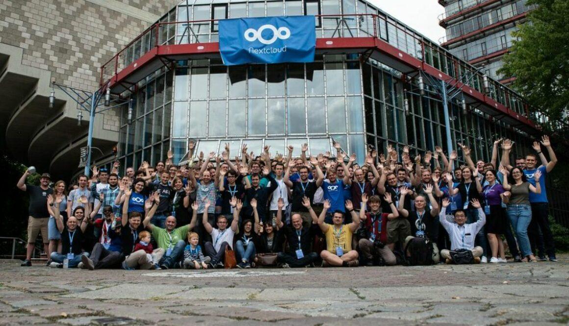 Gente posando en la calle con una bandera de Nextcloud de fondo